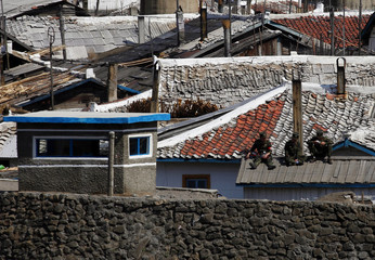 Men sit on a roof near the North Korean city of Hyesan, across the Yalu River from the Chinese town of Changbai