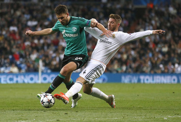 Real Madrid's Ramos and Schalke 04's Szalai fight for the ball during their Champions League last 16 second leg soccer match at Santiago Bernabeu stadium in Madrid