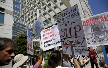 People carry signs during a rally at the Elihu Harris state building in Oakland