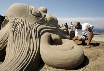 People look at artist Korqaj of Kosovo working on the sand sculpture 'Clown plays elephant' at the Sand Sculptures Festival in Rorschach