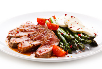 Grilled meat with asparagus and mozarella on white background