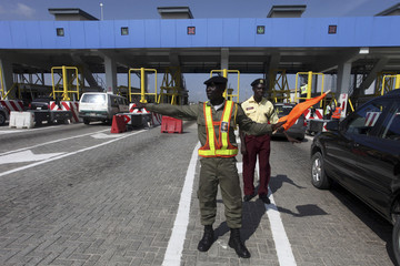 A toll official controls traffic during an initial test of a newly built toll-gate leading to the Lagos free trade zone in Lagos