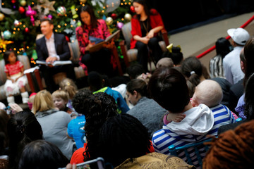 A baby sleeps on her mother's shoulder as television personality Ryan Seacrest and U.S. First Lady Michelle Obama read 'The Night Before Christmas' during their visit with patients at Children's National Medical Center in Washington