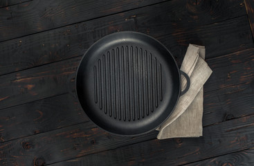 Vintage empty grill pan with napkin on dark wooden background