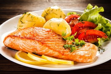 Grilled salmon with potatoes on wooden table