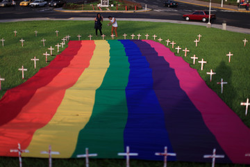 Members of the LGBT community participate in a vigil in memory of the victims of the Orlando Pulse gay nightclub shooting and hate crimes in San Salvador