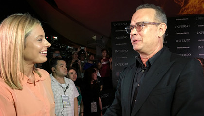 """Actor Tom Hanks speaks to a reporter as he promotes the film """"Inferno"""" on a red carpet in Singapore"""