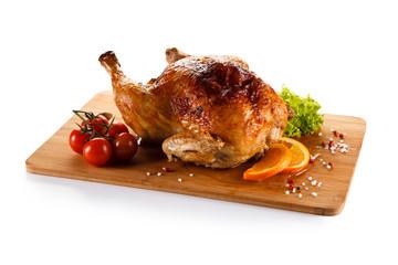 Roast chicken on cutting board on white background