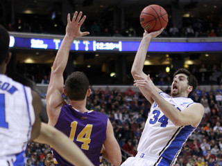 Duke Blue Devils' Kelly shoots over the defense of Albany Great Danes' Rowley during first half of their second round NCAA tournament game in Philadelphia