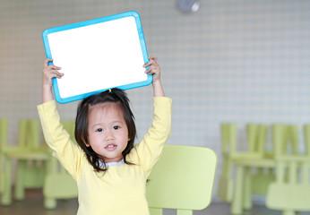 Cute asian child girl holding empty white blackboard in kids room.
