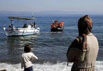 A dinghy overcrowded with Syrian refugees is towed by a Greek fishing boat to the island of Lesbos