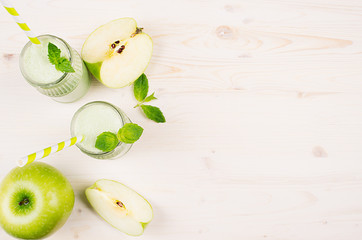 Freshly blended green apple fruit smoothie in glass jars with straw, mint leafs, cut apples, top view. White wooden board background, copy space.