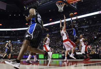 Magic's Howard goes to the basket against Raptors' Gray and Bayless during their NBA basketball game in Toronto