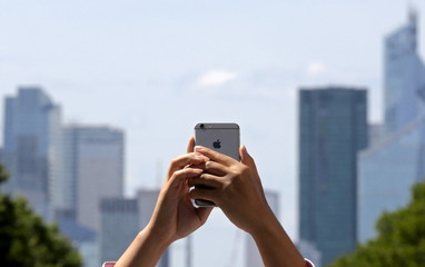 A man raises his mobile phone as he takes pictures on the Champs Elysees avenue in Paris