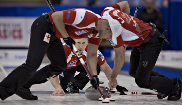 Canada skip Brad Jacobs watches the line of his shot as teammate Ryan and E.J Harnden sweep during their page playoff game against Denmark at the World Men's Curling Championships in Victoria