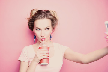 close-up portrait of a beautiful young blonde girl in fashionable sunglasses on a pink background in studio in a dress holding a popular phone smiling It makes selfie drink through a straw drink