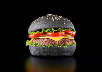 Black burger isolated on black background.