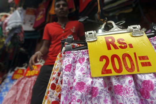 A customer walks out from a clothing stall as a price list of the shop's goods are seen near a main market in Colombo