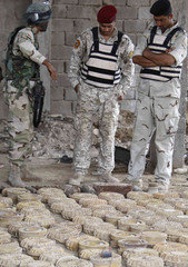 Soldiers look at confiscated mines and ammunition after a raid and search operation at an industrial area in Basra
