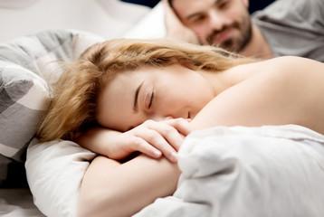Loving family sleeping in bed