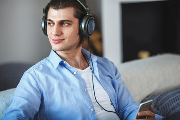 Handsome guy sitting on sofa with headphones
