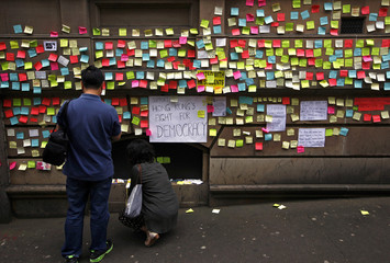 People write messages of support for pro-democracy protesters in Hong Kong, on paper to stick to the wall of Hong Kong House in central Sydney