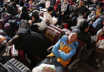 A passenger rests in the waiting room of the Beijing Railway Station during the travel rush ahead of the upcoming Spring Festival in Beijing