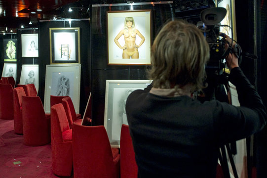 A camerawoman films the Pin Up exhibition at Crazy Horse cabaret in Paris