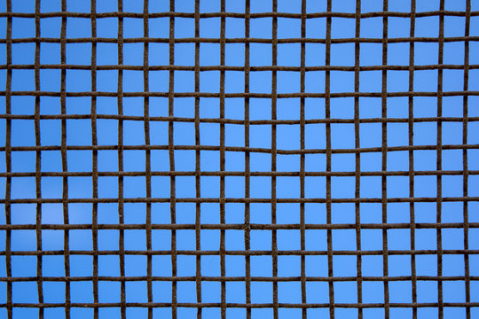 Photo of steel mesh wall on sky background