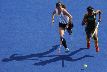 Argentina's Mariela Scarone and South Africa's Sulette Damons run after the ball during their women's Group B hockey match at the London 2012 Olympic Games at the Riverbank Arena on the Olympic Park in London