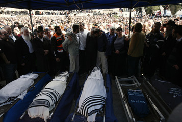 Mourners stand around the bodies of Ehud Fogel, his wife Ruti and their children during their funeral in Jerusalem