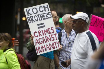 """A protester holds up a sign against the Koch Brothers at the """"People's Climate March"""" down 6th Ave. in Manhattan, New York"""