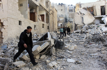 Men inspect a site hit by what activists said was an airstrike by forces loyal to Syria's President Bashar al-Assad in the al-Sukkari neighbourhood in Aleppo