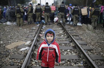 A migrant child stands on rail tracks while waiting to cross the border from Greece into Macedonia, near Gevgelija