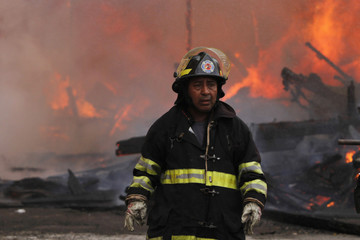 A firefighter is seen as wooden houses burn in the background at the El Chorrillo neighborhood in Panama City