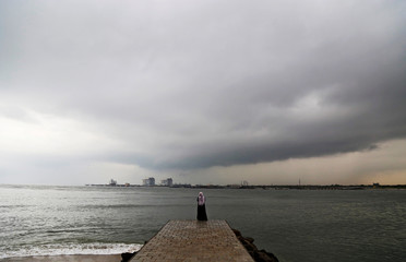 A woman stands on a seaside promenade against the background of pre-monsoon clouds gathered over the Arabian Sea in Kochi