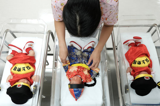 A nurse takes care of newborn babies wearing Chinese traditional costumes to celebrate the Chinese New Year at the nursery room of Paolo Chockchai 4 Hospital, in Bangkok