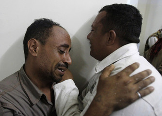 Men mourn a relative killed by shelling of forces loyal to Yemen's President Ali Abdullah Saleh in the southern city of Taiz