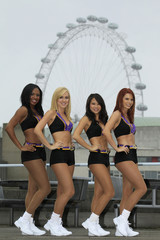 Four members of the 'Laker Girls' pose for a photograph in front of the London Eye, in London