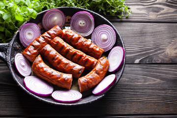 Grilled sausage in a pan and fresh herbs on wooden table