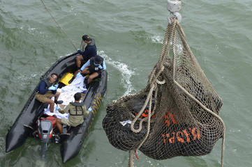Indonesian Navy frogmen and underwater demolition unit personnel on a boat carrying bodies from AirAsia flight QZ8501, look as a body is lifted to the Indonesian Navy vessel KRI Banda Aceh, at sea