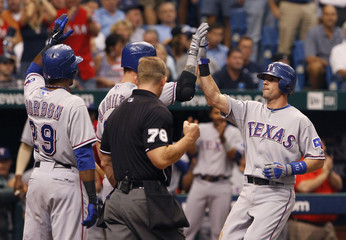Texas Rangers hitter Young is congratulated by teammates after his fifth inning three-run home run during play against the Tampa Bay Rays during their American League Division Series MLB baseball game in St. Petersburg