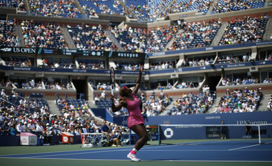 Serena Williams of the U.S. serves to compatriot Vania King at the 2014 U.S. Open tennis tournament in New York