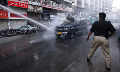 A supporter of the Pakistan Islamist party Pasban is hit by a jet of water from a police vehicle during a protest march towards the U.S. consulate in Karachi