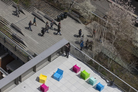 An attendee takes a photo as people walk on the High Line below at The Whitney Museum of American Art in New York