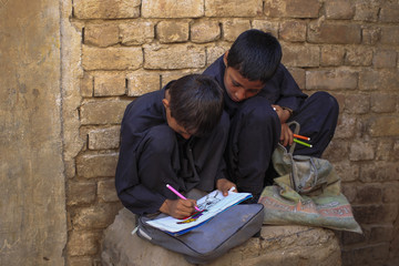 A boy uses colour markers to fill his drawing book outside his makeshift school on the outskirts of Islamabad.