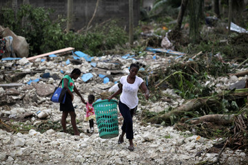 A woman carries a laundry basket in an area devastated by Hurricane Matthew in Cavaillon, Haiti