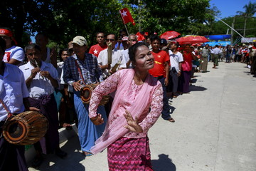 Myanmar ethnic Rakhine people dance as they welcome Myanmar's pro-democracy leader Aung San Suu Kyi during her campaign rally for the upcoming general elections in Thandwe