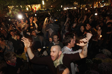 Members of the Occupy Wall St movement react after an announcement that a planned cleaning has been suspended in Zuccotti Park