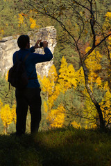 Tourist taking photo of an autumnal forest